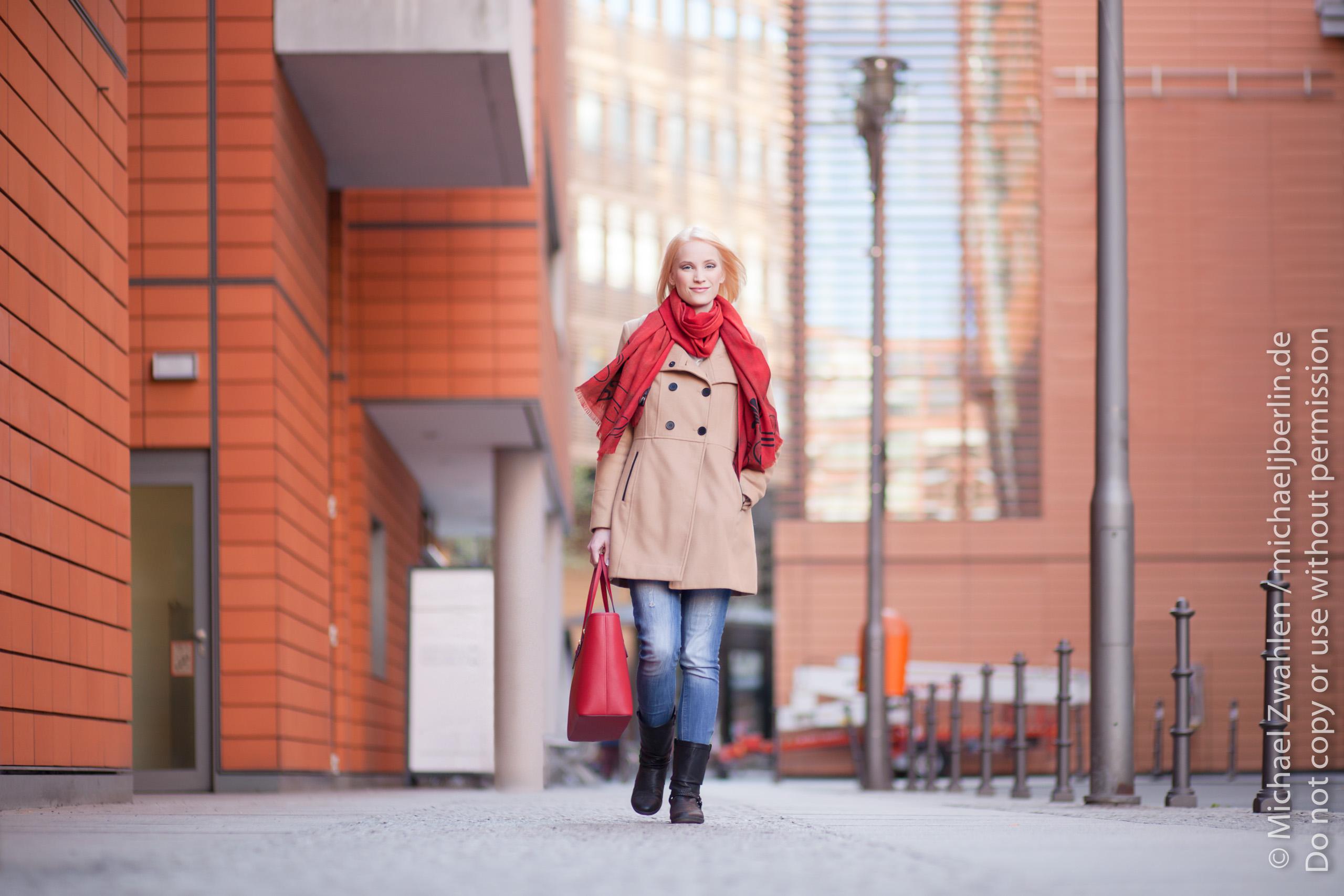 Junge Frau läuft Strasse entlang, mit Geschäften im Hintergrund. Berlin, Deutschland.