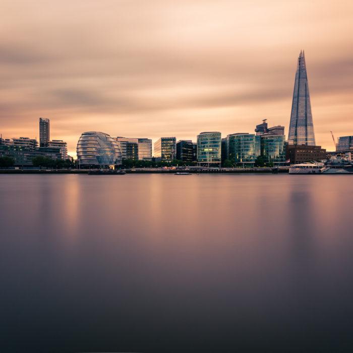Langzeitbelichtung von Skyline moderner Geschäftshäuser über der Themse bei Sonnenuntergang in London, United Kingdom.