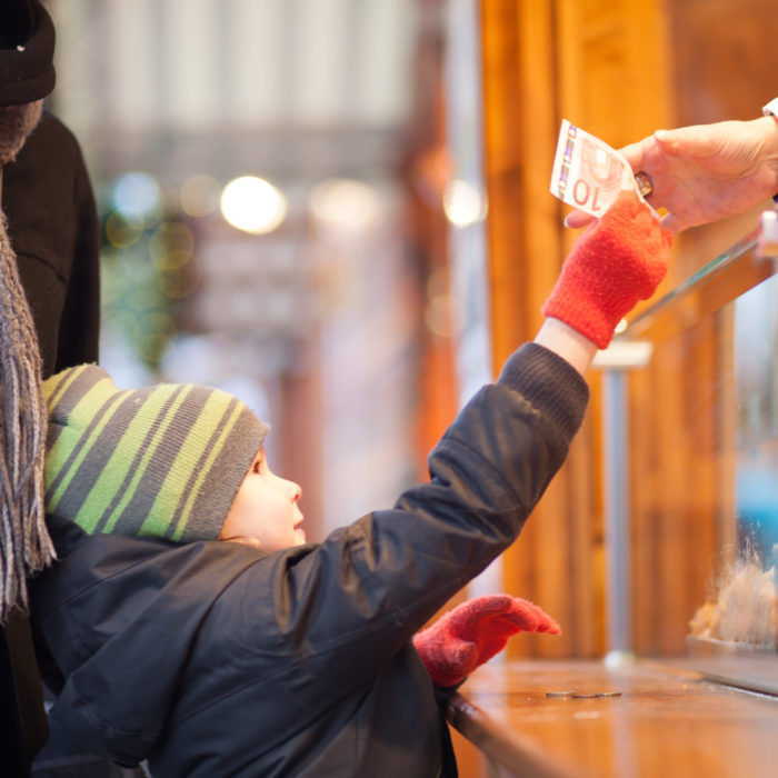 Mother with son, standing on a Christmas market booth, boy handing money to the vendor. Berlin, Germany.