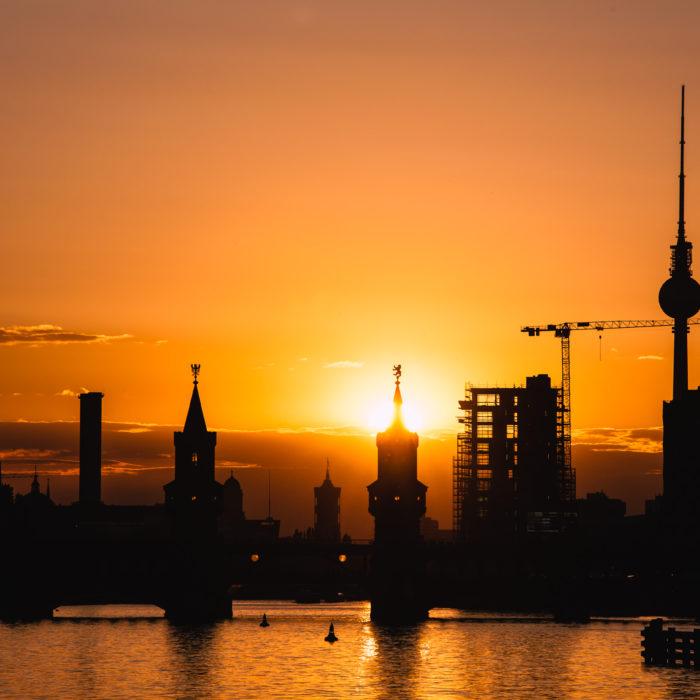 Silhouette der Oberbaumbrücke und Fernsehturm hinter der Spree bei Sonnenuntergang. Berlin, Deutschland.