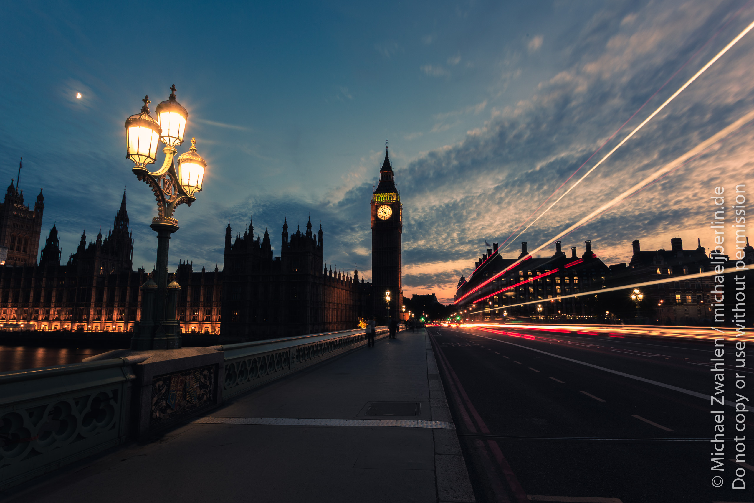 Light trails of passing cars and bus on Westminster Bridge, with Big Ben in the center, moon and clouds in the sunset sky. London, England, United Kingdom.